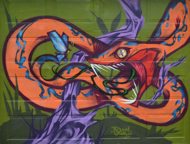 mural of an orange and blue snake loosely tied in a knot around a purple tree, blue butterfly hovers in front of snake's face, mural by Cruz 1