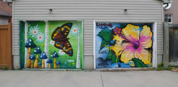 a mural on a garage door in an alley, part of butterflyways project - two adjacent garage doors, the left one is by mska and is a brown butterfly and mushrooms. on the right is an hibiscus flower by horus taffytats